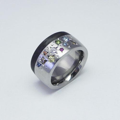 Ring aus Edelstahl mit Carbon. Farbige Brillanten mit Sternchen gefasst.