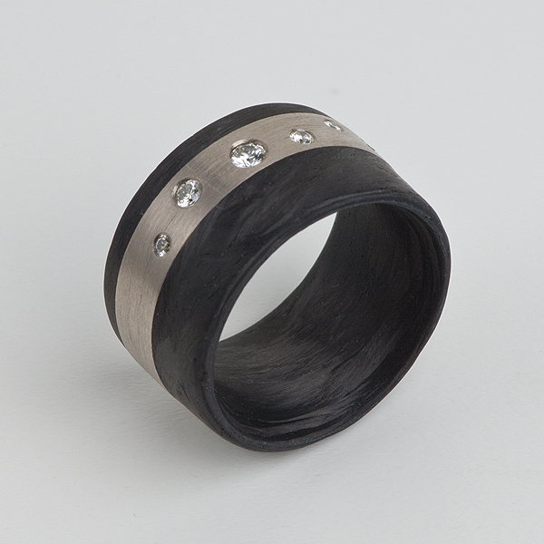 Ring aus Carbon mit 18 Karat Weissgold. In dem Weissgoldstreifen sind Kundensteine gefasst.