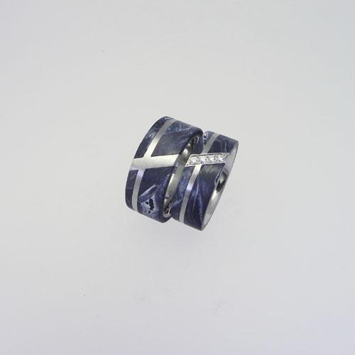 Trauringe aus Palladium mit grauem Carbon. Die Partnerringe werden durch eine Diagonale verbunden. Im Damenring sind Brillanten gefasst
