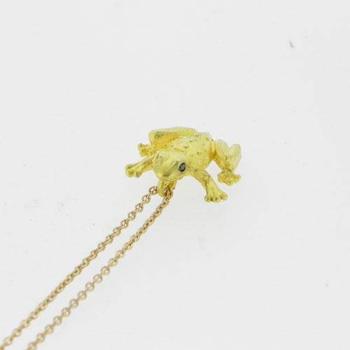 Ein Frosch aus Gold mit zwei kleinen schwarzen Diamanten