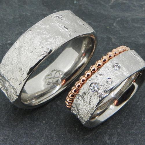 Eheringe mit individueller Steinstruktur. Beide Ringe aus Platin. Der Damenring hat einen Vorsteckring aus Perldraht in Rotgold