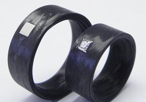 Partnerringe aus Carbon. Im Damenring ist ein Brillant gefasst und im Herrenring ein Quadrat aus Weissgold eingearbeitet.