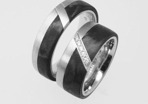 Trauringe aus Platin mit Carbon. Im Damenring ist die Diagonale mit Brillanten ausgefasst.