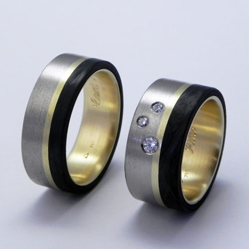 Partnerringe aus Gelb-und Weissgold mit schwarzem Carbon. Im Damenring wurde ein vorhandener Ehering umgearbeitet und der Herrenring wurde passend dazu angefertigt.